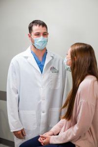 Dr. Alex Laudenklos consulting with a patient at Faith Regional Physician Services OB/GYN