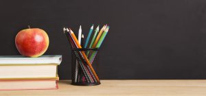 School books, apple and pencils over chalkboard background